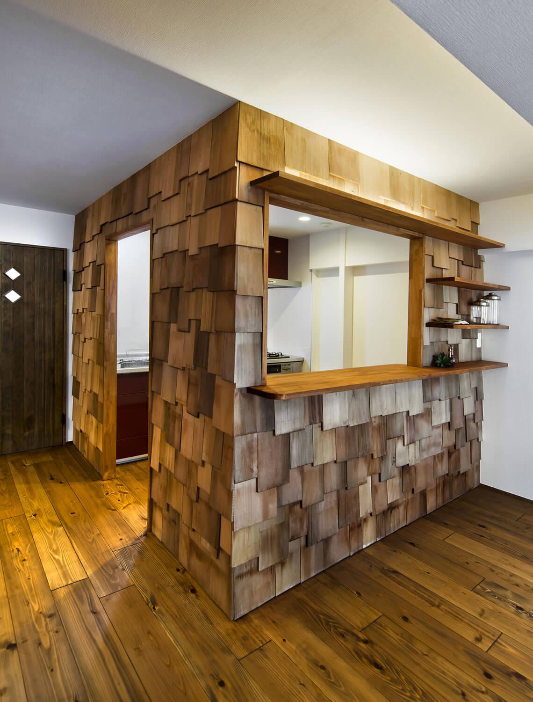廃材のような板をつけたキッチンスペースの画像